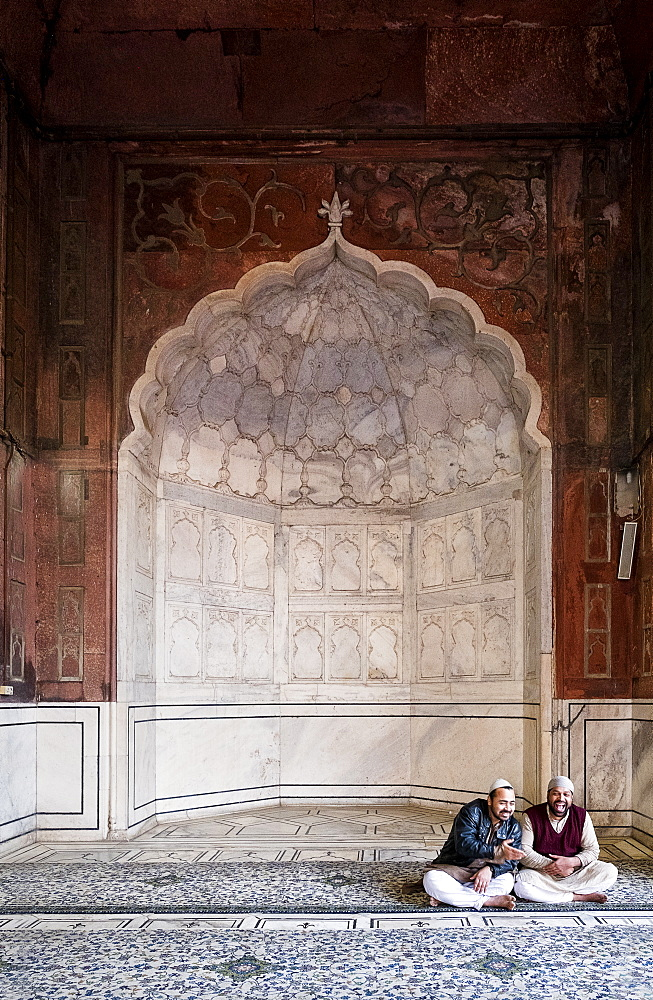 Men sitting by arch at Jama Masjid mosque in Delhi, India, Asia - 1111-47