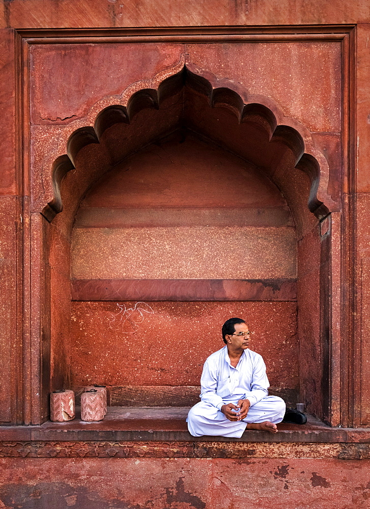 Portrait Muslim man in arch, Jama Masjid, one of the largest mosques in India.