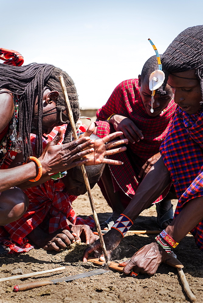 Masai men lighting fire using traditional methods, Masai Mara Village in National Reserve, Kenya, East Africa, Africa