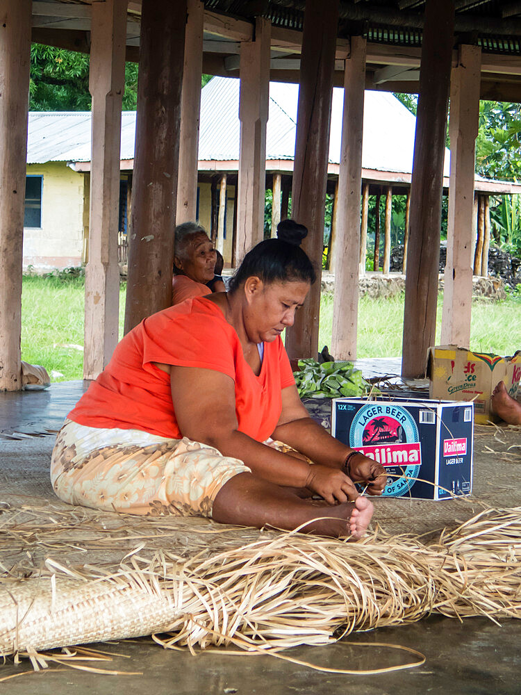 Woman with children weaving traditional mats in the town of Lufilufi on the island of Upolu, Samoa.