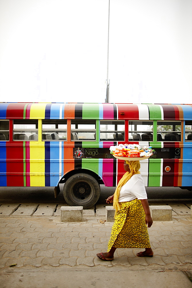 Merchant passing a school bus, Cotonou, Littoral Department, Benin