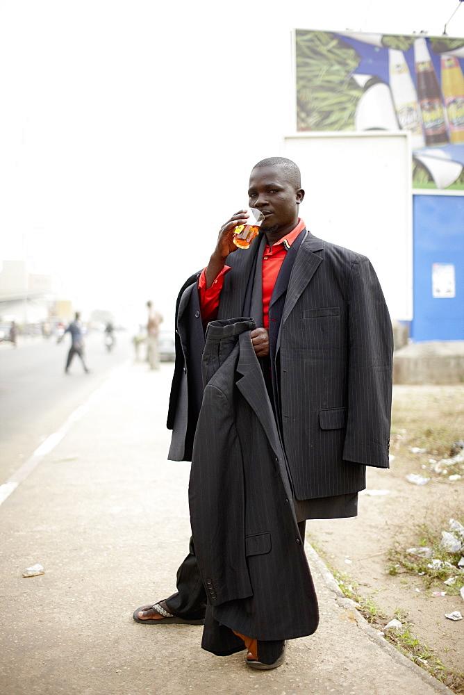 Merchant selling suits at main street, Ganxi, Cotonou, Benin
