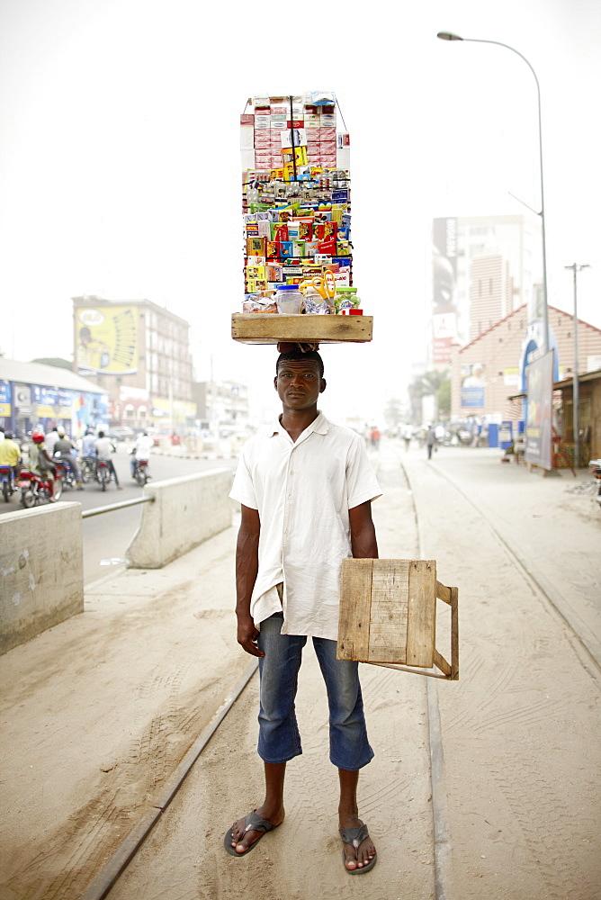 Merchant carrying a mobile kiosk, Ganxi, Cotonou, Benin