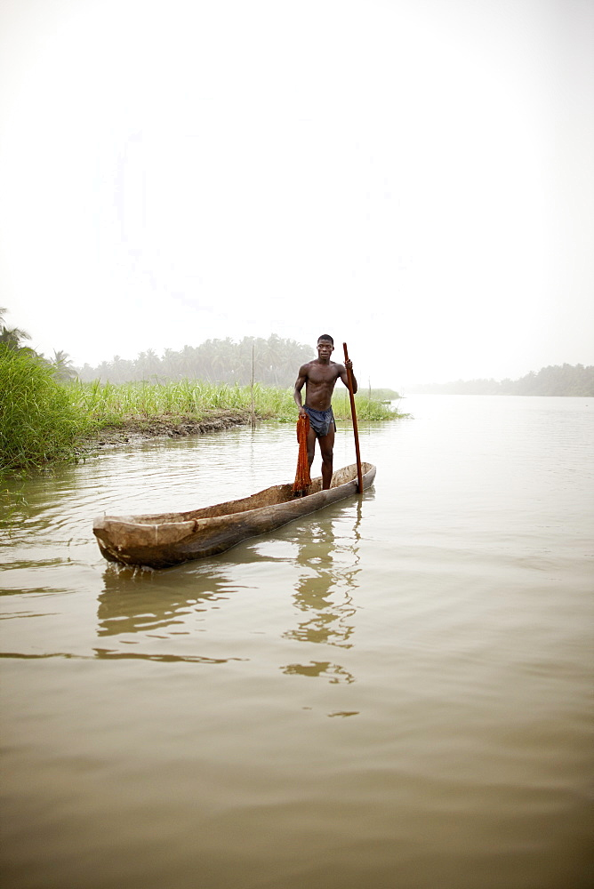 Man in a logboat fishing on Mono river, Agbanakin, near Grand-Popo, Mono Department, Benin