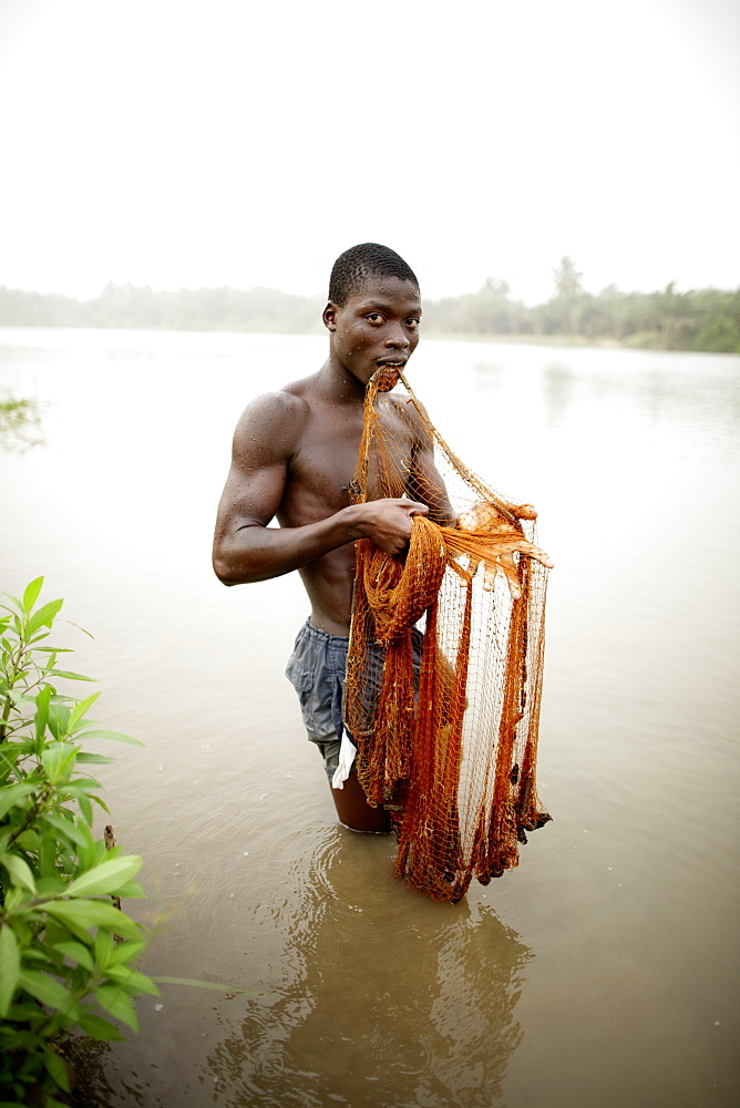 Young man fishing with cast net in river Mono, Agbanakin, near Grand-Popo, Mono Department, Benin