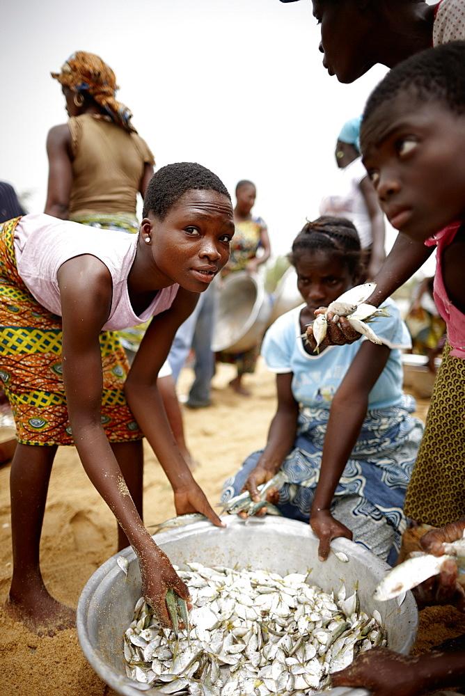 Woman and children selecting trawl fish catch, Grand-Popo, Mono Department, Benin