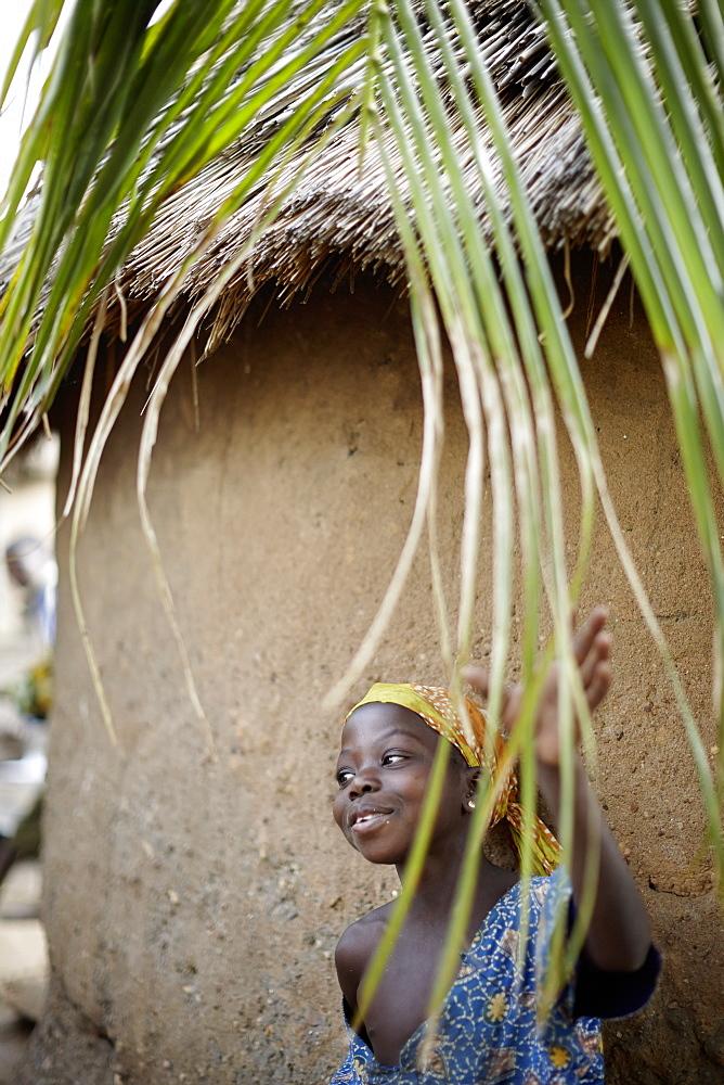 Girl in front of a hut, Taneka-Beri, Benin