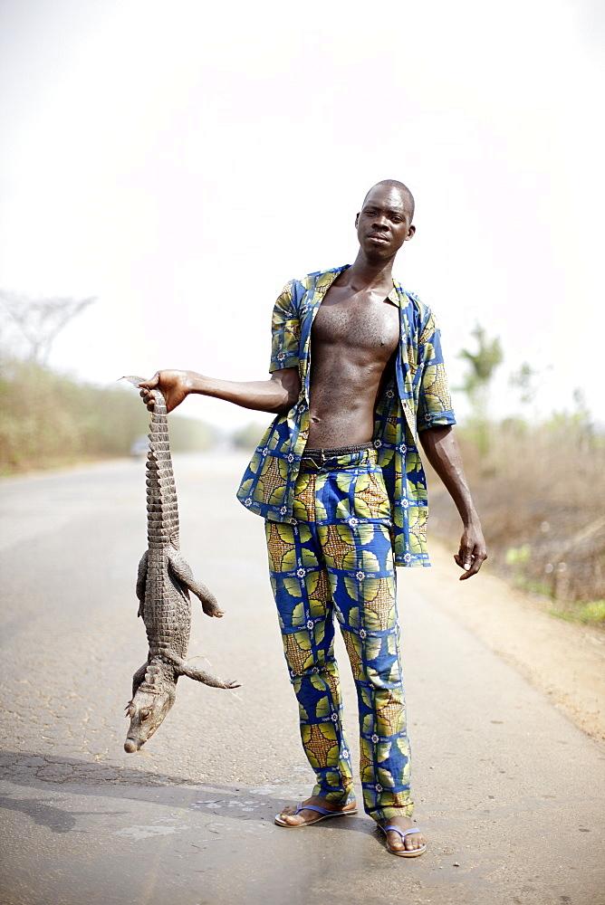 Man selling crocodile at national road, Abomey, Zou Department, Benin