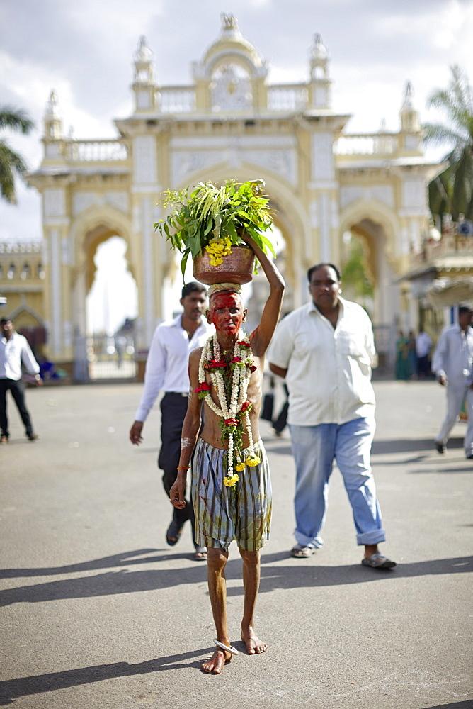 Pilgrim carrying holy water, gate to Amba Vilas Palace in background, Mysore, Karnataka, India