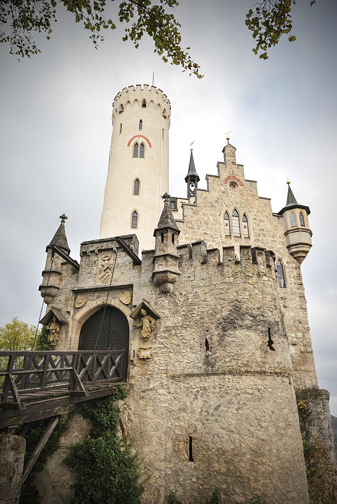 View of Lichtenstein castle with draw-bridge in autumn, Swabian Alp, Baden-Wuerttemberg, Germany