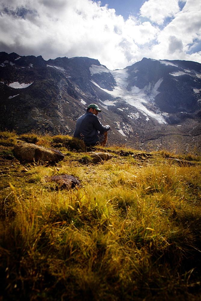 Man sitting on a mountain meadow, rear of Gschnitz Valley (ca. 2413 m), Stubai Alps, Tyrol, Austria