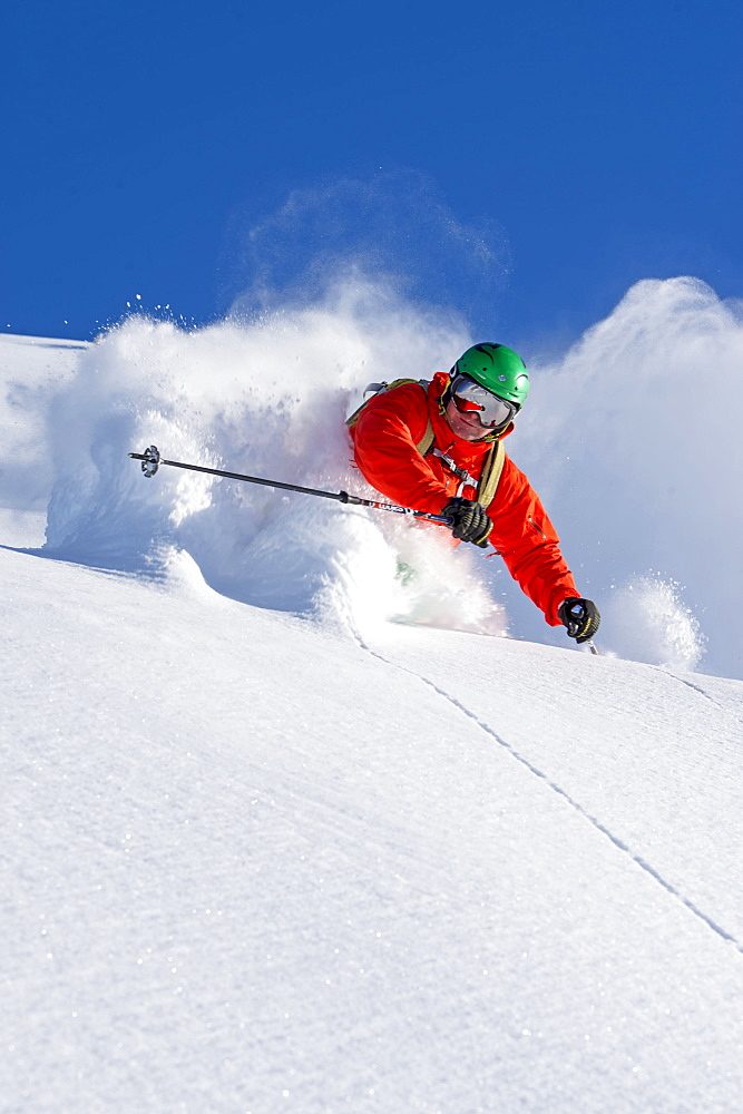 Closeup of a skier in waistdeep powder turning in front of the camera, Hochfuegen, Zillertal, Austria - 1113-102441
