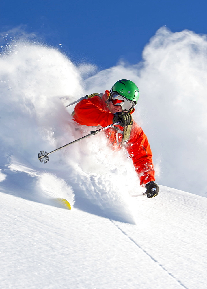 Closeup of a skier in waistdeep powder turning in front of the camera, Hochfuegen, Zillertal, Austria