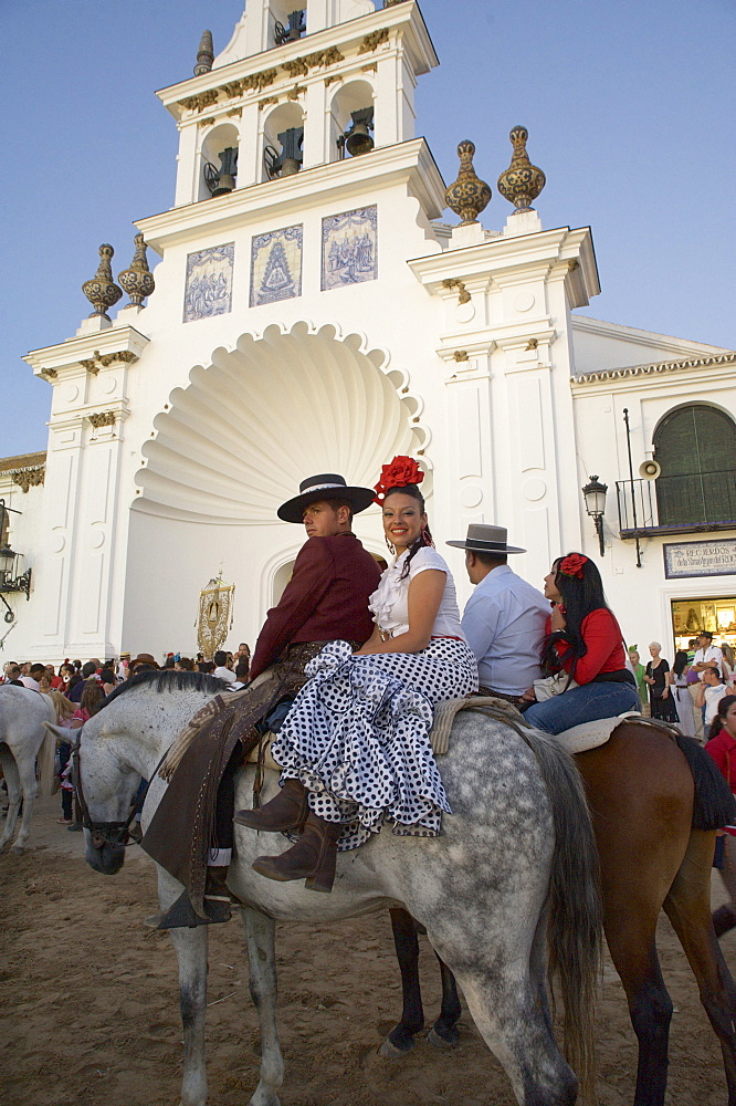 Couple on horseback in traditional dress in front of the church Eremita del Rocio at El Rocio at Pentecost, Huelva, Andalusien, Spanien
