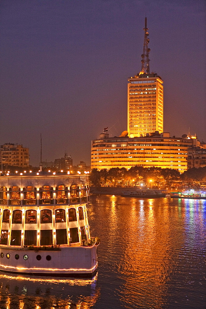 Illuminated ship on the Nile in front of the high rise building of the egyptian television center, Cairo, Egypt, Africa