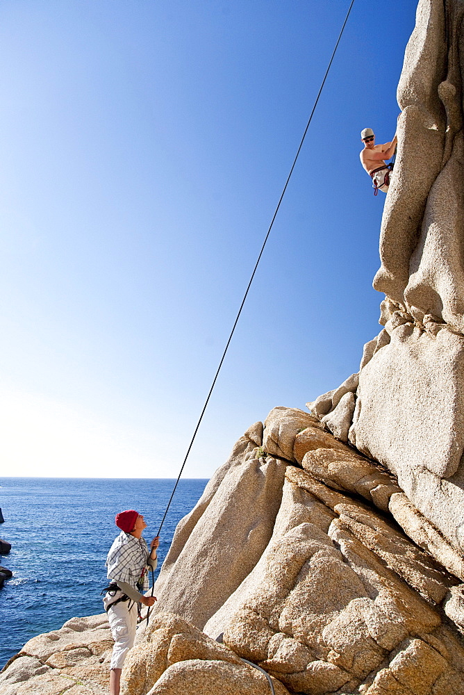 Climbers on a granitic rock on shore under blue sky, Capo Testa, Santa Teresa Gallura, Sardinia, Italy, Europe