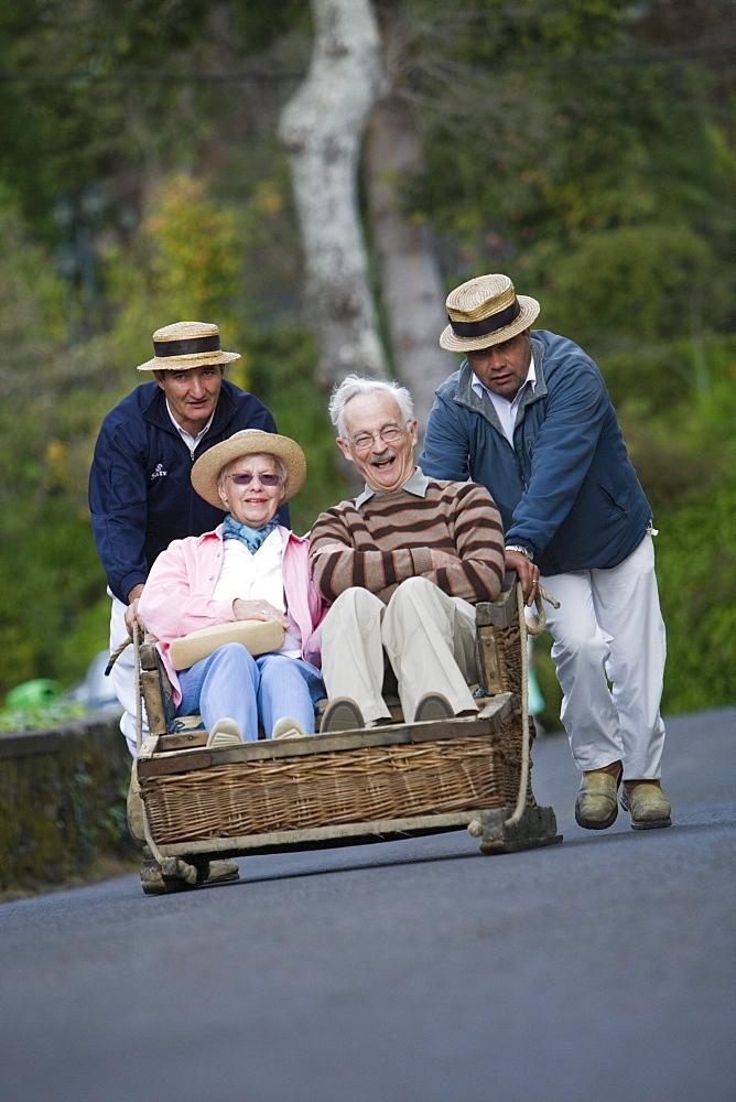 Elderly couple enjoying a Monte Toboggan Run, Funchal, Madeira, Portugal