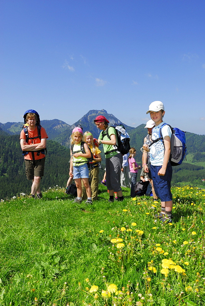 Group of hikers with children standing on meadow, Bavarian Alps, Upper Bavaria, Bavaria, Germany