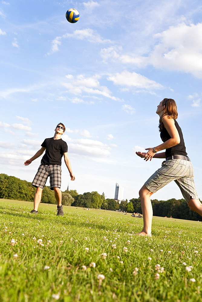 Young people playing volleyball on a meadow, Leipzig, Saxony, Germany