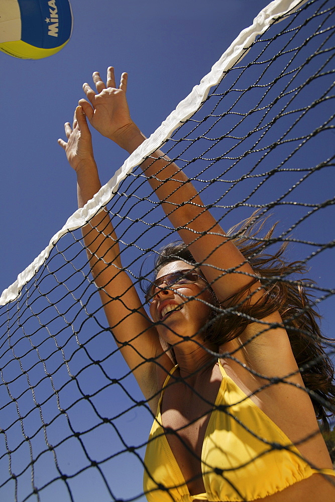 Young woman playing volleyball, wearing a yellow bikini, Mallorca, Balearic Islands, Spain