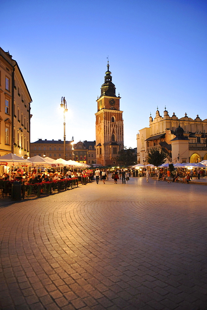 Town hall tower at Rynek glowny, market place with street cafes in the evening, Krakow, Poland, Europe