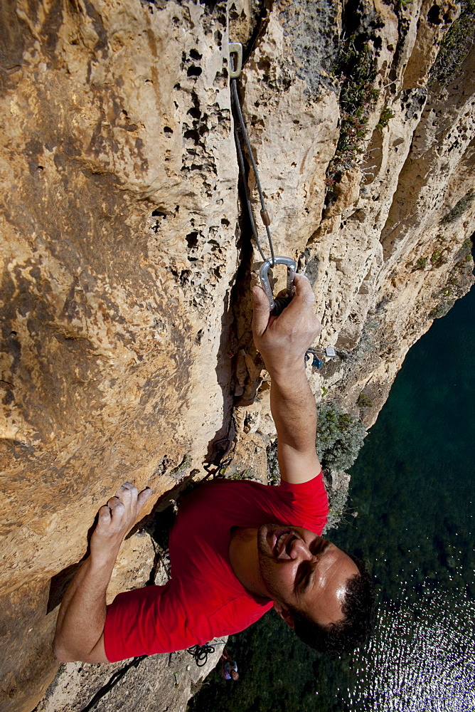 A young man climbing above the Inland Sea, he places natural protection, Dwerja Bay, Gozo, Malta, Europe