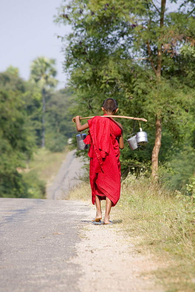 Young burmese monk carrying water tnks over his shoulders near Mount Popa, Myanmar, Burma