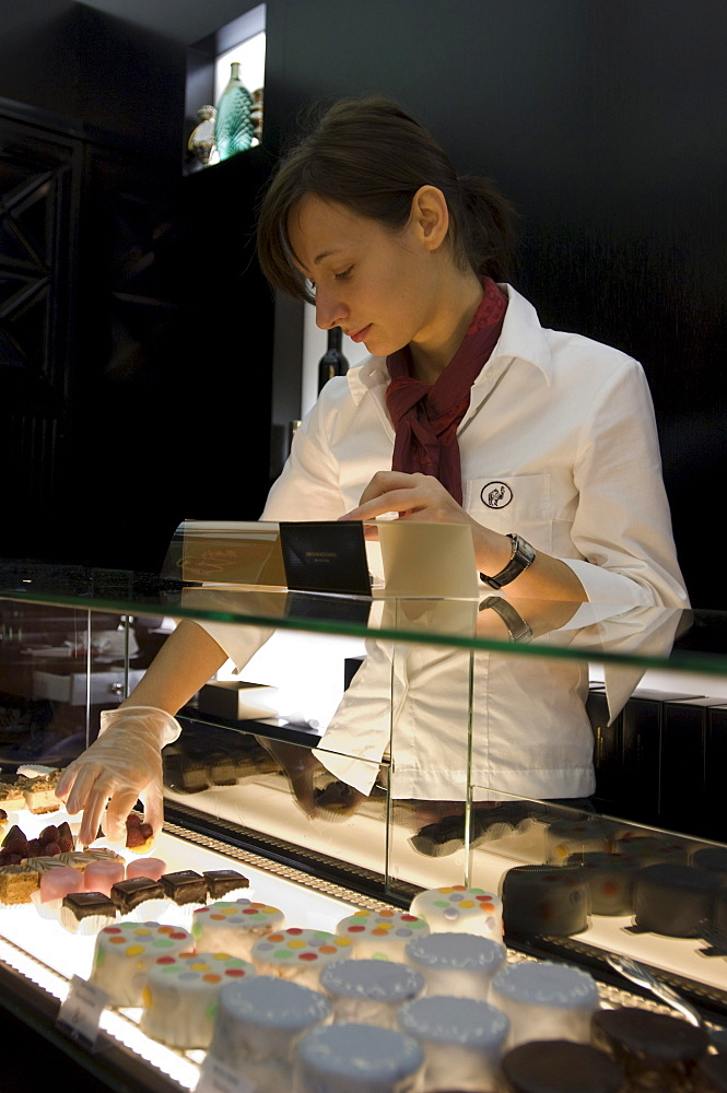Sales girl with pralines in the Patisserie Zum Schwarzen Kameel, Vienna, Austria