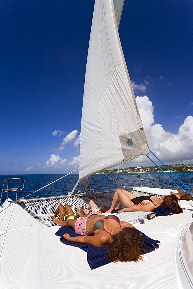 Women sunbathing on a catamaran, West Coast, Barbados, Caribbean