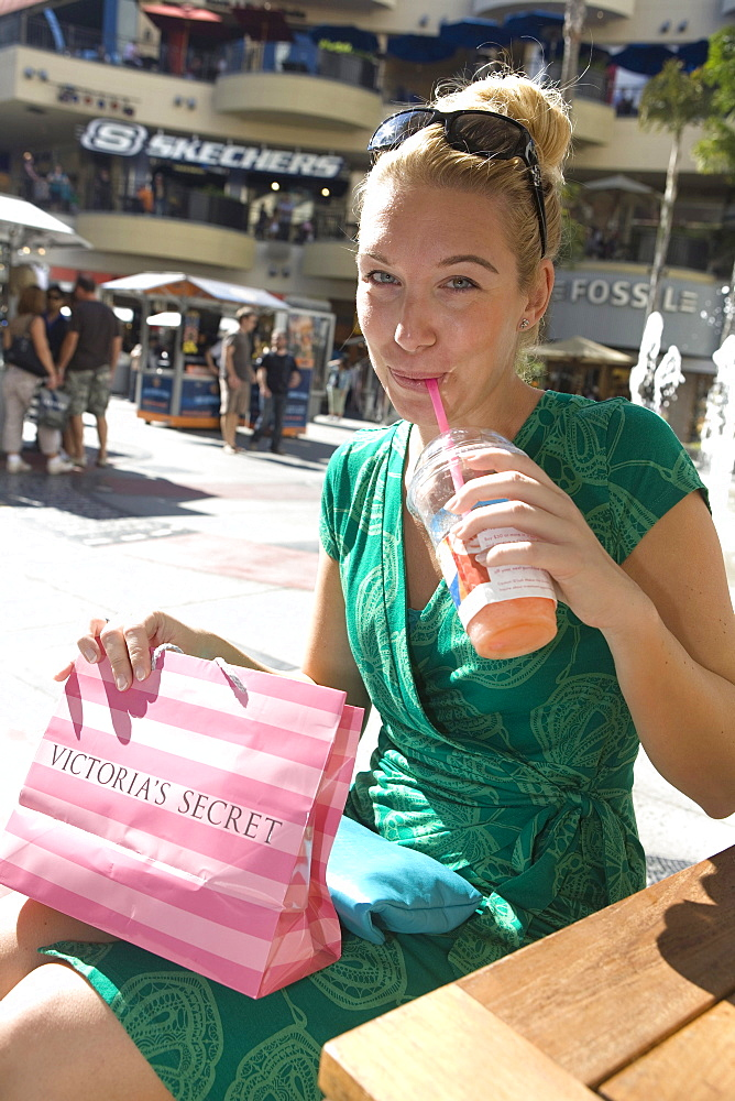 Woman enjoying a drink in a cafe after a shopping tour in the Kodak theatre complex, Graumans Chinese Theater, Hollywood, Los Angeles, California, USA