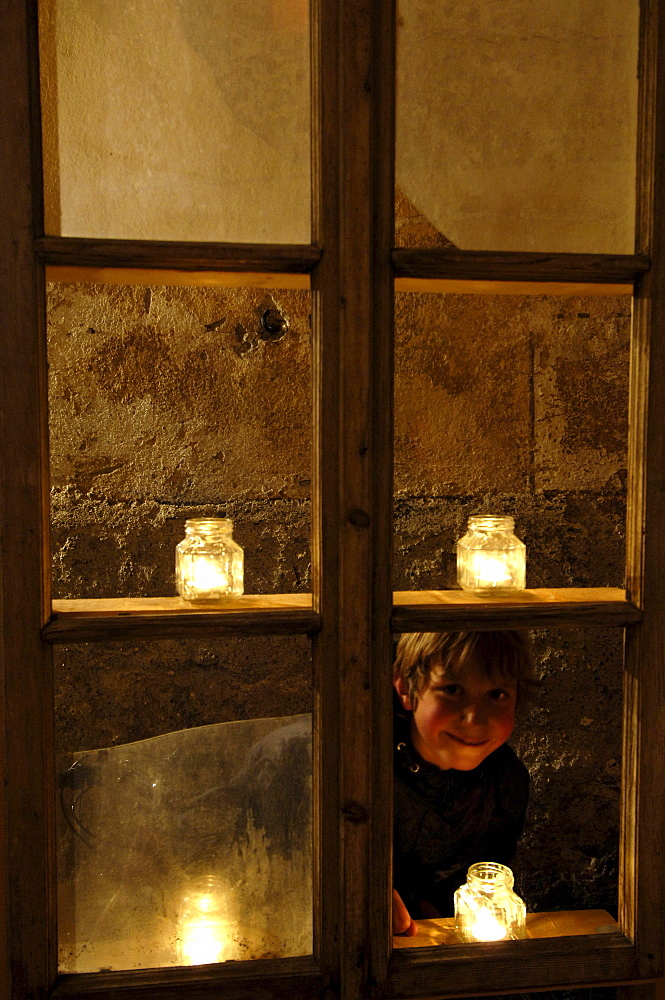 A boy looking through a candle-lit window at the christmas market, Glurns, Val Venosta, South Tyrol, Italy, Europe