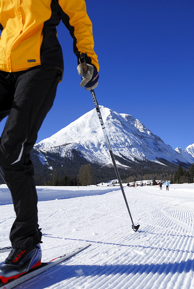 Woman cross-country skiing, Hohe Munde in background, Leutasch, Tyrol, Austria