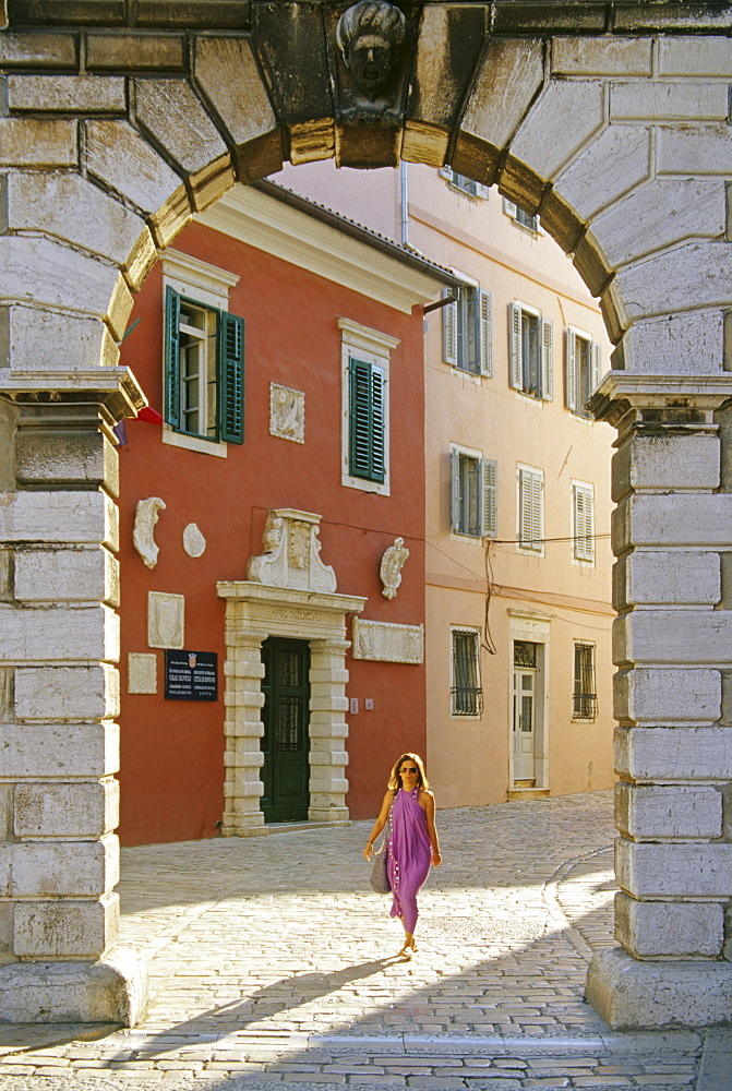 A woman and venetian Balbi gate at the Old Town of Rovinj, Croatian Adriatic Sea, Istria, Croatia, Europe