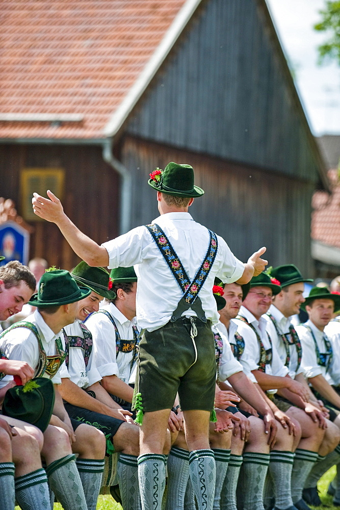 Young men wearing traditional costumes sitting side by side, May Running, Antdorf, Upper Bavaria, Germany