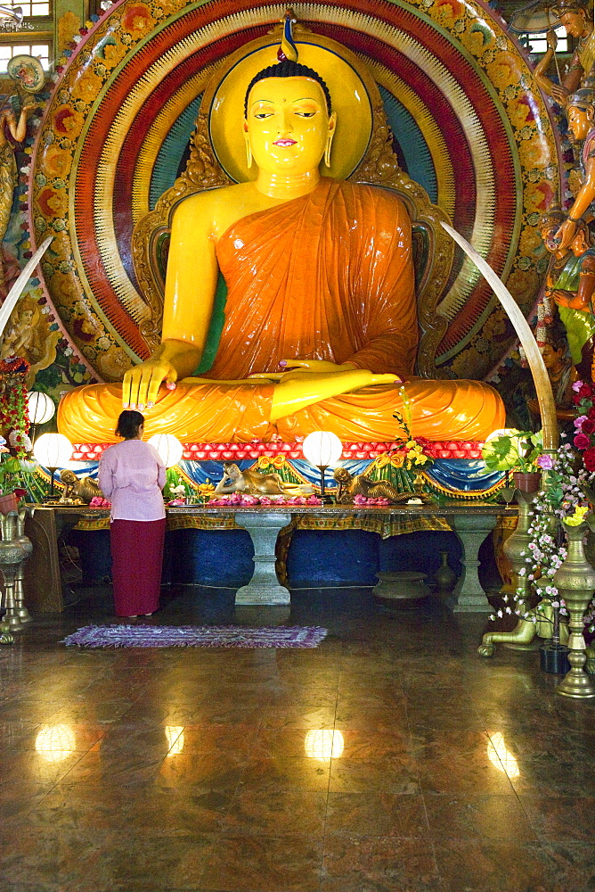 Woman in front of a big Buddha statue in the Gangaramaya temple, Colombo, Sri Lanka, Asia