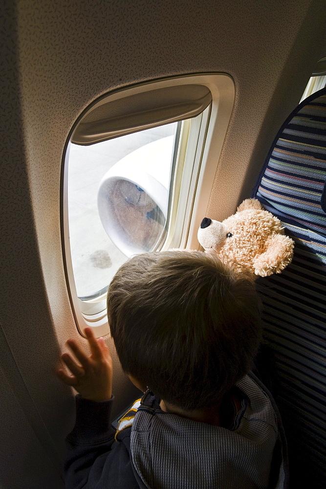 Boy looking through airplane window, Munich airport, Bavaria, Germany