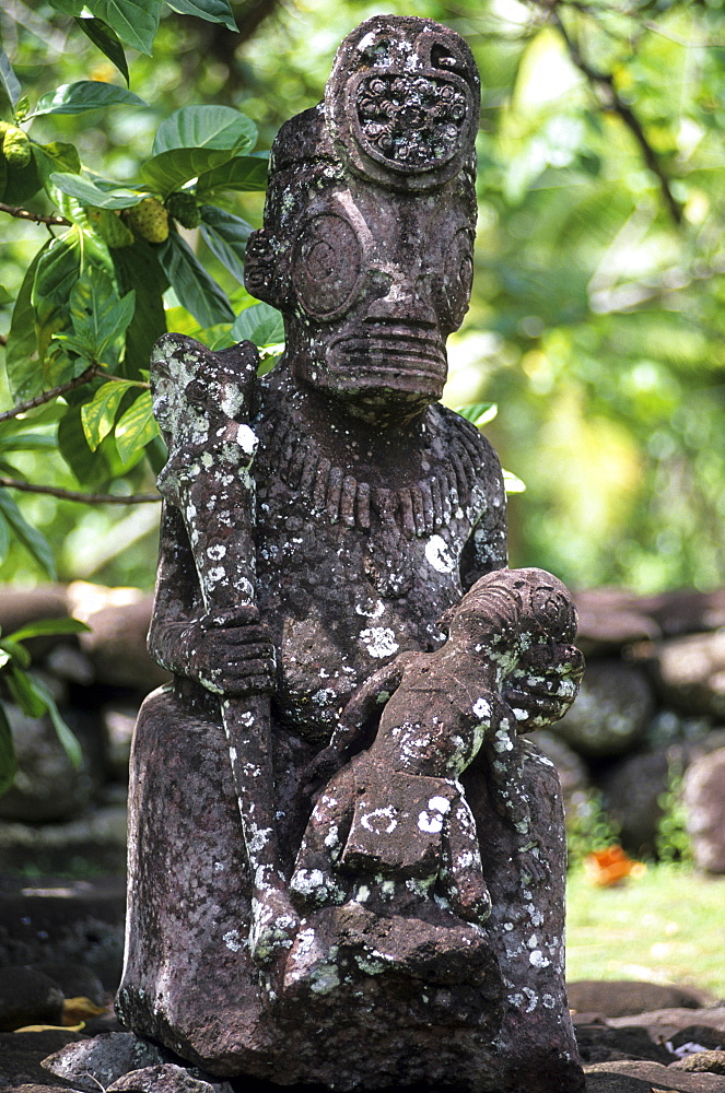 Weather beaten statue made of stone, Tiki in the village of Hatiheu on the island of Nuku Hiva, French Polynesia