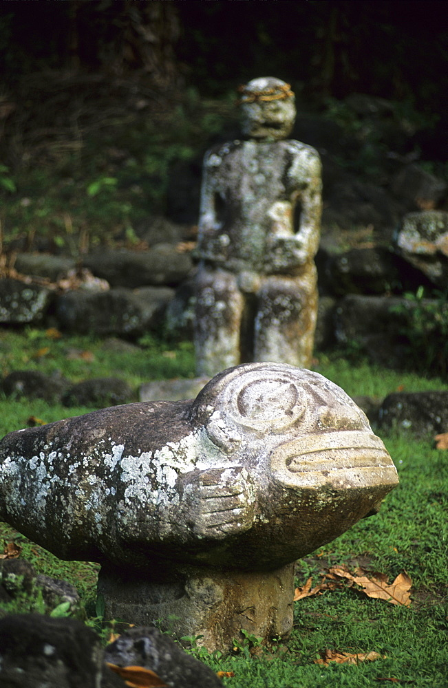 Weather beaten stone statues at an archaeological site in the village of Hatiheu on the island of Nuku Hiva, French Polynesia