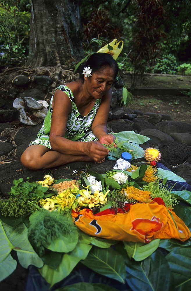 A native woman binding bouquets of flowers in the village of Omoa, island of Nuku Hiva, French Polynesia