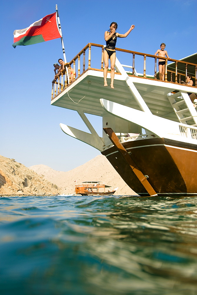 Woman jumping from a boat into the sea, Boat with tourists, Dhow, Haijar Mountains, Musandam, Oman