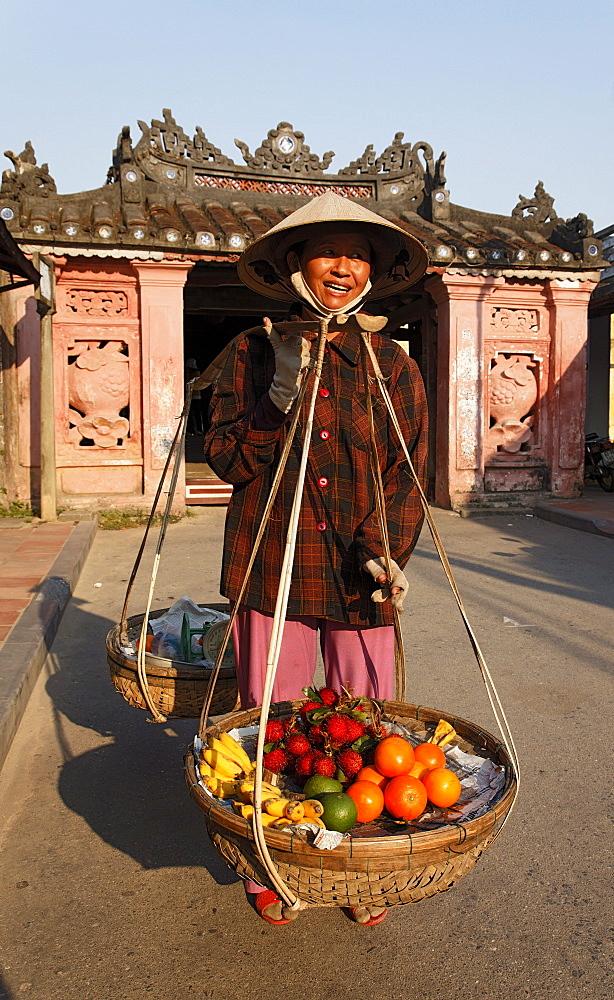 Woman with baskets passing Chua Cau, Japanese Bridge, Hoi An, Annam, Vietnam