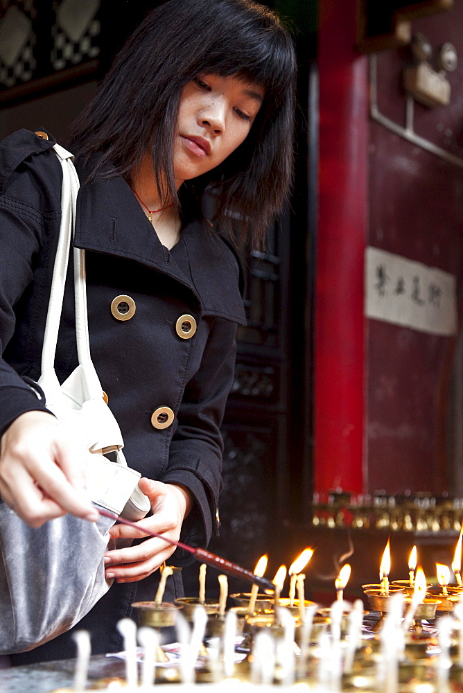 Oil lamps and butter lamps, woman lighting a candle, buddhist ritual, Luohan Temple, buddhist temple downtown, Chongqing, People's Republic of China