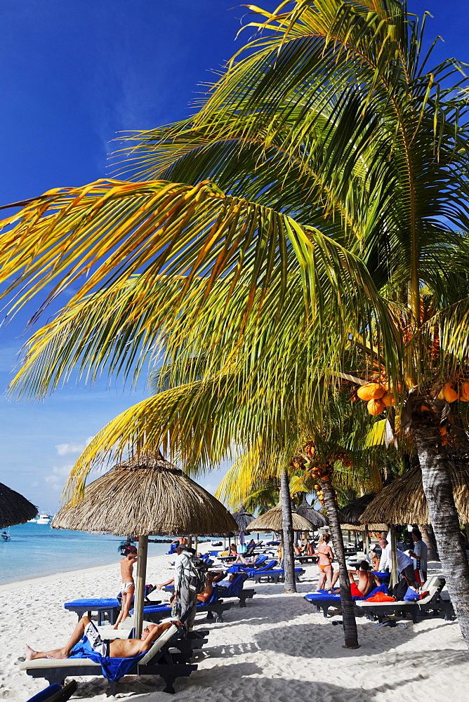 Palm trees and people on the beach of Beachcomber Hotel Paradis & Golf Club, Mauritius, Africa