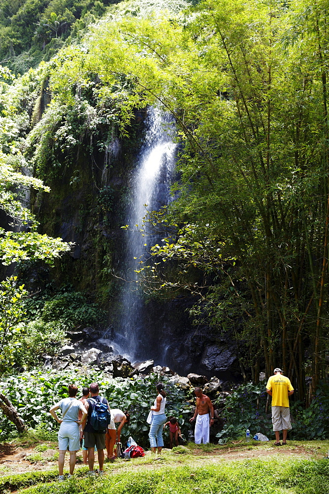 People in front of a waterfall at Anse des Cascade in Bois-Blanc, La Reunion, Indian Ocean