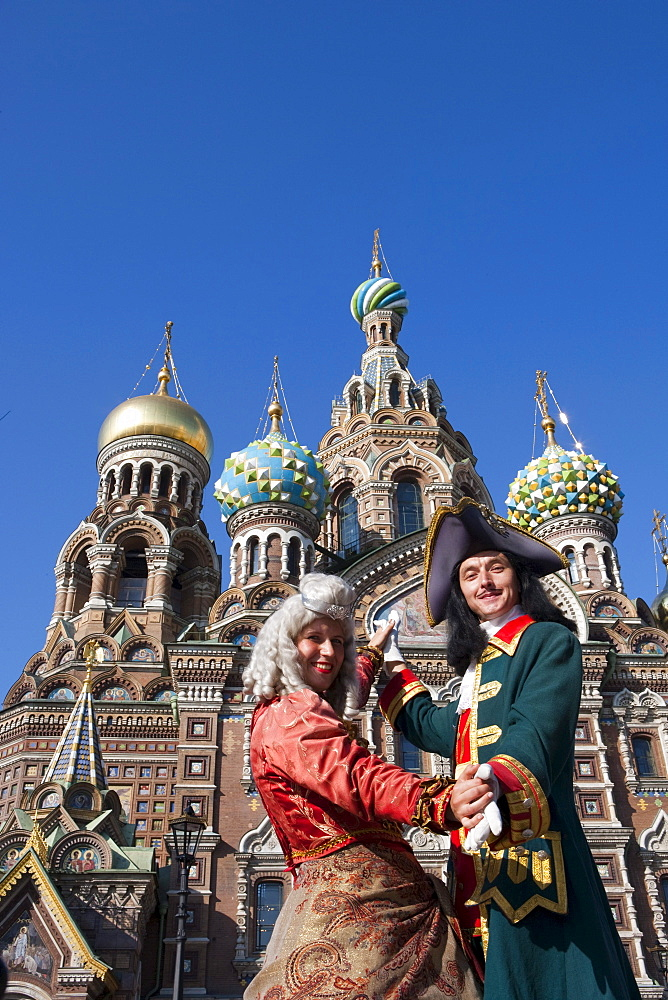Couple in historic costumes pose as Empress and Tsar in front of Church of the Savior on Spilled Blood, Church of the Resurrection, St. Petersburg, Russia