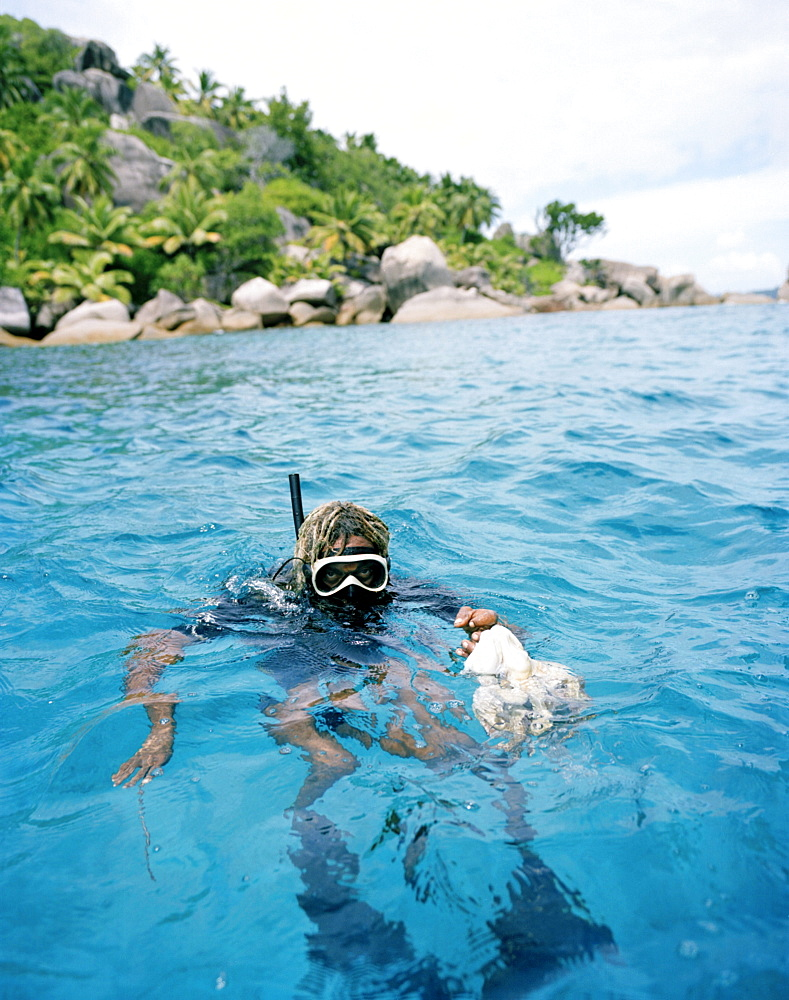 Octopus hunter Alvis Jean snorkeling off FelicitÈ island with squid, Coleoidea, La Digue and Inner Islands, Republic of Seychelles, Indian Ocean