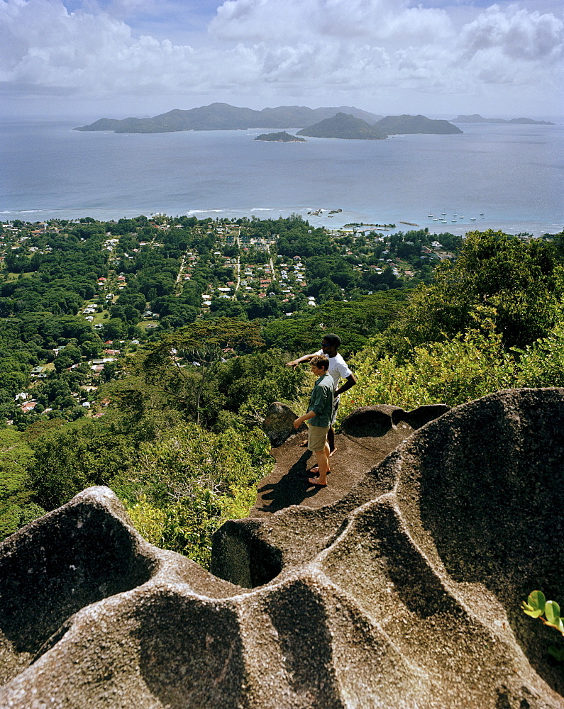 Hikers on granitic rock on the way to Nid d'Aigles lookout point in 300m above sealevel, view over the village La Passe and Praslin Island, central La Digue, La Digue and Inner Islands, Republic of Seychelles, Indian Ocean