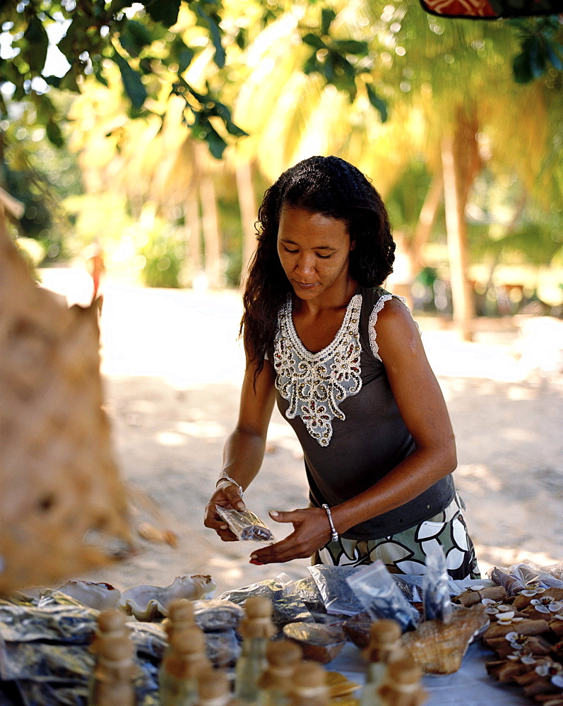 Woman is selling souvenirs and coconuts, south western La Digue, La Digue and Inner Islands, Republic of Seychelles, Indian Ocean