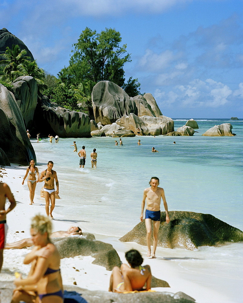 Tourists on worlds most famous beach Anse Source d'Argent with its granitic rocks, south western La Digue, La Digue and Inner Islands, Republic of Seychelles, Indian Ocean