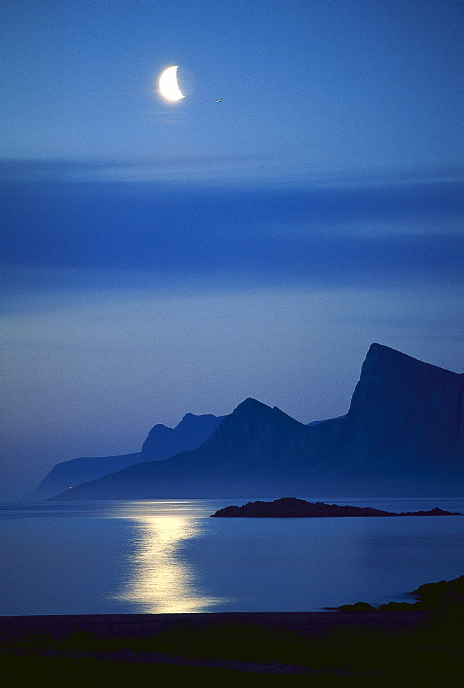 Moon above ocean and coast area, Flakstad, Lofotes, Norway, Europe